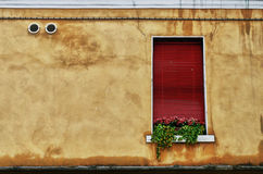 Red window on a tanned wall Stock Photos