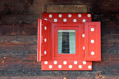 Red window on wooden wall Royalty Free Stock Photo