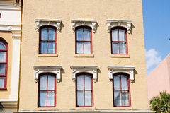 Red Windows in Old Brown Brick Building Royalty Free Stock Photos