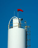 Red windsock atop storage tank Royalty Free Stock Images