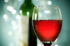 Red Wine. A full glasss of red wine with glitter lights in the background Royalty Free Stock Images