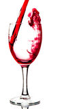 Red wine. Being poured into a wine glass isolated on a white background stock images