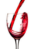 Red wine. Being poured into a wine glass isolated on a white background royalty free stock photos