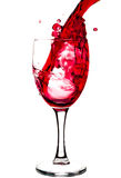 Red wine. Being poured into a wine glass isolated on a white background Stock Image