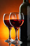 Red wine. Glasses and bottle of red wine over yellow background Royalty Free Stock Images