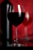 Red wine. The big glass of red wine and bottle on a red background Royalty Free Stock Photography