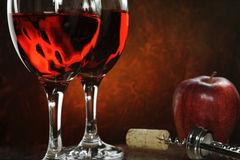 Red Wine. And apple with abstract red background Royalty Free Stock Photos