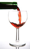 Red wine. Being poured into a wine glass and a green bottleneck Stock Images