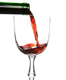 Red wine. Being poured into a wine glass and a green bottleneck Royalty Free Stock Images