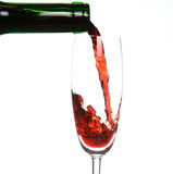 Red wine. Being poured into a wine glass and a green bottleneck Stock Image