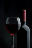 Red wine. The big glass of red wine and bottle on a dark background Royalty Free Stock Image