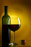 Red wine. The big glass of red wine and bottle on a yellow background Stock Images