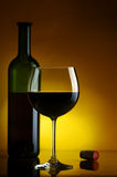 Red wine. Bottle and glass of wine on a yellow background Royalty Free Stock Image
