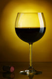 Red wine. Glass of wine on a yellow background Royalty Free Stock Photo