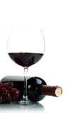 Red wine. Bottle of red wine and red grapes on a white background Stock Images
