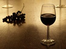 Red wine. Glass of red wine with with grapes in the background Stock Photos