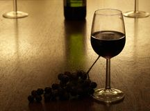 Red wine. Glass of red wine with with grapes and a bottle of red wine in the background Royalty Free Stock Photos