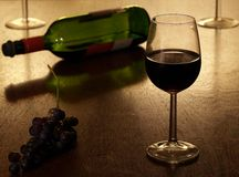Red wine. Glass of red wine with with grapes and a bottle of red wine in the background Stock Photos