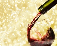 Red wine. Pouring red wine and holiday lights Royalty Free Stock Photography