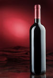 Red wine. Bottle of red wine on a red background Royalty Free Stock Images