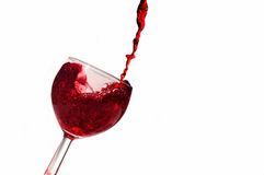 Red wine. Splash into glass isolated on white background Stock Photos