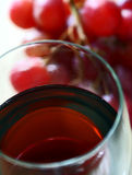 Red wine. Close up of red wine with red grapes on background royalty free stock images
