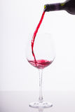 Red wine. Is being poured into a big wine glass Royalty Free Stock Image