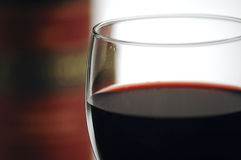 Red Wine. Close up of red wine in a glass with a bottle in the background. Extreme shallow depth of focus Royalty Free Stock Images
