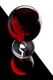 Red wine. A wineglass containing red glass on the edge of a black glass table Stock Images