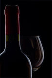 Red wine. A bottle of red wine with a glass  on a dark filed Stock Photography