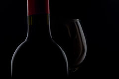 Red wine. A bottle of red wine with a glass  on a dark filed Stock Photos