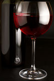 Red wine. Glass of red wine and bottle on black background Royalty Free Stock Photos