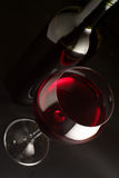 Red wine. Glass of red wine and bottle on black background Stock Photography