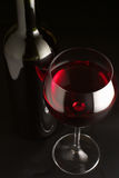 Red wine. Glass of red wine and bottle on black background Royalty Free Stock Photography