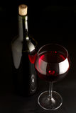 Red wine. Glass of red wine and bottle on black background Royalty Free Stock Images