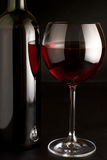 Red wine. Glass of red wine and bottle on black background Stock Image