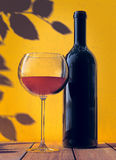 Red wine. Glass and bottle on orange background Royalty Free Stock Photos