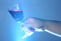 Red wine. Give in hand and blue light Royalty Free Stock Image
