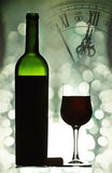 Red wine against holiday lights and clock Royalty Free Stock Photos