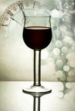 Red wine against holiday lights and clock Royalty Free Stock Image