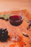 Red wine against wooden background Stock Photos