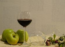 Red wine, apples and roses on the table stock photos