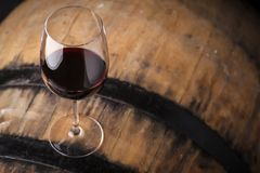 Red wine on a barrel. Glass of red wine standing on an oak barrel in a cellar royalty free stock image