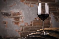 Red wine on a barrel. Glass of red wine standing on an oak barrel in a cellar stock photo