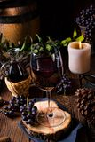Red wine from a barrel with grapes and a glass of wine Stock Photography