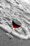 Red wine at beach. A glass of red wine in on a black and white beach stock images