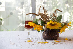 Red wine in a beautiful glass and a bouquet of sunflowers Stock Images