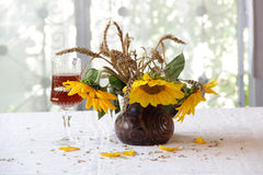 Red wine in a beautiful glass and a bouquet of sunflowers Royalty Free Stock Images