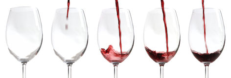 Red wine being poured. Into wineglass, white background Royalty Free Stock Image