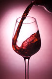 Red wine being poured. A bottle of red wine being poured in a glass Royalty Free Stock Photography